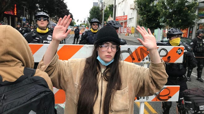 A protester stands with her hand up in front of a road blocked by Seattle police in the Capitol Hill Organized Protest zone early Wednesday, July 1, 2020. Police in Seattle have torn down demonstrators' tents in the city's so-called occupied protest zone after the mayor ordered it cleared.