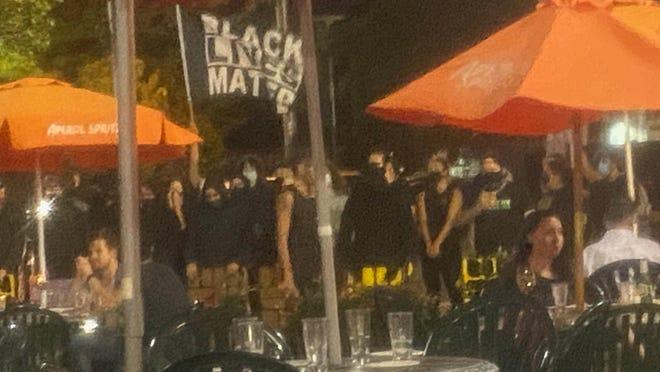 Protesters gather near Venda Bar & Ristorante on Tuesday night.