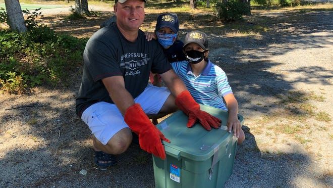 Jason Snell of Harwich and his sons, Cooper and Colton, sit at Johnny Kelley Park in Dennis on Thursday with a male red-tailed hawk in a Rubbermaid container. Jason found the bird on Route 6 and brought his family to see its release after rehab.