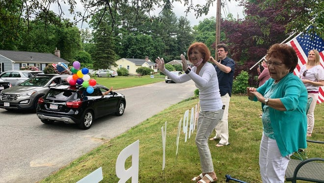 Sarah Cammarata, far right, waves to well-wishers during a drive-by 101st birthday celebration for her, joined by her daughter, Roseann Shorette, middle, and other family members.