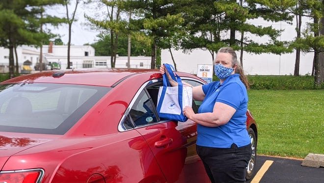 Morton Public Library staff member Patty Howard delivers library materials to a patron as part of the library's Book Valet curbside service.