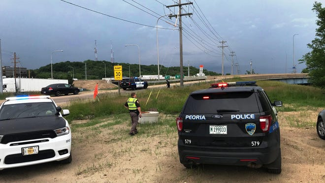 Police vehicles are parked along Adams Street at the McClugage Bridge in Peoria. They were pursuing two men who jumped from the bridge, according to a police spokeswoman.