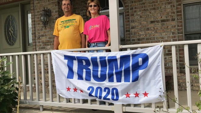 """Robert and Natalie Stash stand behind a Trump sign on their front porch in Pekin. They cut off the bottom section of the sign that, according to a Pekin code-enforcement officer, included a word that constituted """"immoral, obscene or indecent matter."""""""