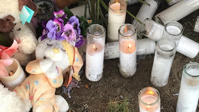 Some candles continue to burn Tuesday at an impromptu memorial set up at Washington and Darst streets, where four young woman died in a car wreck early Sunday.