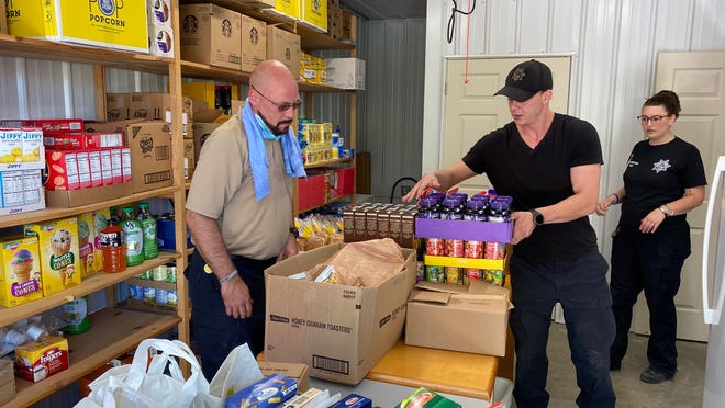 Correction officers Robert Brunner, left, Jacob Last, middle and  Tolisa Blumenstein deliver stacks of food to Holy Family Food Pantry Tuesday in memory of  the last Allissa Martin.