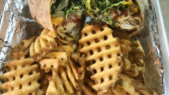 The Southwest Chicken Wrap with waffle fries from Fire & Ale.