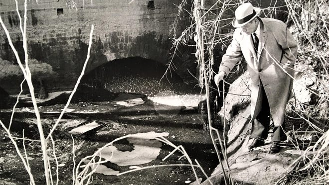 County Commissioner S. Herbert Elliott Sr. points out floating sewage in the Augusta Canal in January 1960.