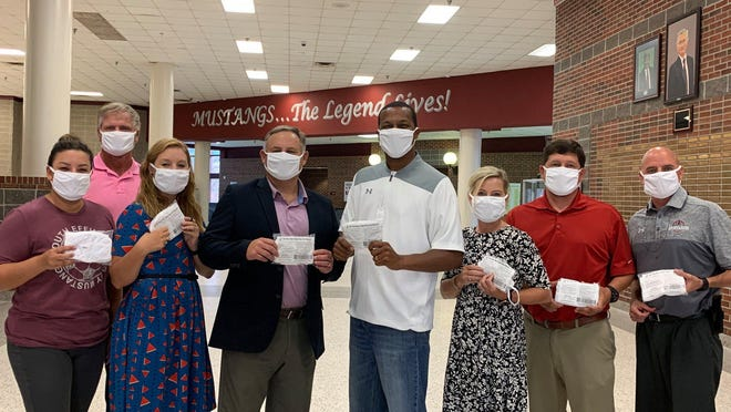 Superintendent Yancy Ford, fourth from left, helped distribute 15,000 face masks the school system received from the state this week. Students will not be required to wear masks but they will be available for those who choose to wear them.