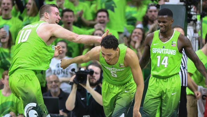 Michigan State basketball players, from left, Matt Costello, Bryn Forbes and Eron Harris celebrate a 74-65 win over the Maryland Terrapins on Jan. 23, 2016, at the Breslin Center in East Lansing.