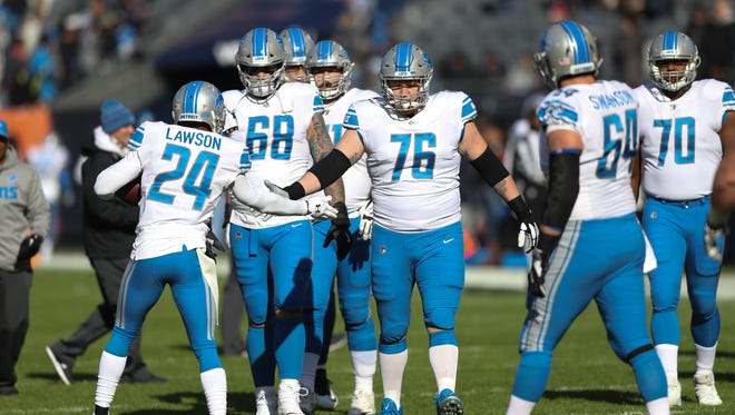 The Detroit Lions, led by T.J. Lang (76), take the field before the game against the Chicago Bears, Nov. 19, 2017 at Soldier Field in Chicago.