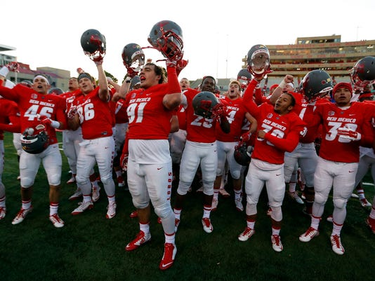 New Mexico players celebrate after beating Utah State 14-13 in an NCAA college football game in Albuquerque, N.M., Saturday, Nov. 7, 2015. (AP Photo/Andres Leighton)