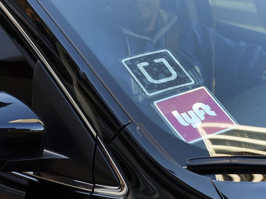 A driver displays their Lyft and Uber stickers on his