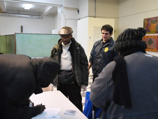 Donald Ames, a team leader at Montclair Emergency Services for the Homeless, and Joe Fayad, a security guard, look on as a man signs in on Thursday, Dec. 28, 2017 at the shelter in Montclair.