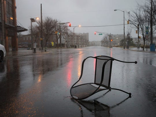 A metal chair that was blown by the heavy winds sits in the middle of a deserted Cookman Ave, in Asbury Park as the nor'easter becomes mainly a rain event for those towns along the shore.