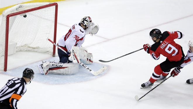 A shot by New Jersey Devils left wing Taylor Hall (9) enters the net behind Washington Capitals goaltender Braden Holtby (70) for an overtime goal in an NHL hockey game Thursday, Jan. 18, 2018, in Newark, N.J. The Devils won 4-3.