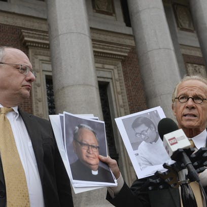 Attorney Jeffrey Anderson, right, holds pictures of Fr. Anthony Marfori at a news conference March 16 announcing a second lawsuit against Marfori, who used to teach at Cathedral High School. With him is Attorney Mike Bryant.