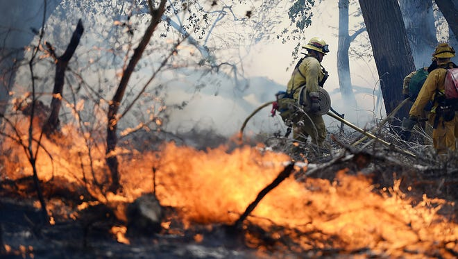 Firefighters battle a wildfire in The Mojave Narrows Regional Park in Victorville Calif., Tuesday, March 31, 2015.