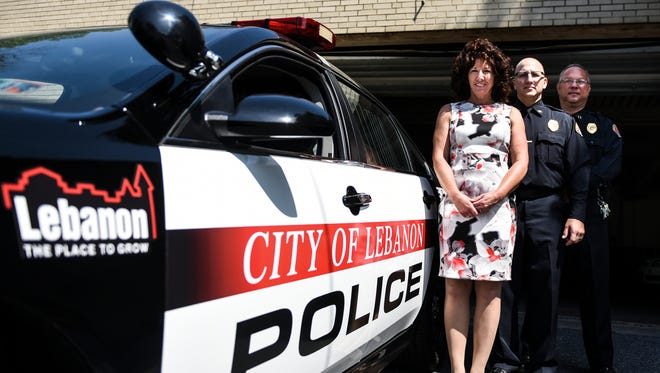 """Lebanon Mayor Sherry Capello, Chief Todd Breiner and Captain David Gingrich stand in beside one of three new police cars the city recently purchased. The cruisers have a new design, sporting black, white and red colors and a decal of the city's logo """"Lebanon a Place to Grow."""""""