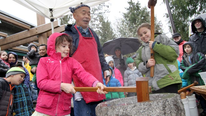 Shoichi Sugiyama works with children Pearl Abbott, 7, left, and Loren Logghe, of Bainbridge Island, to pound the rice ball at the annual Mochi Tsuki festival Sunday on Bainbrdige Island.
