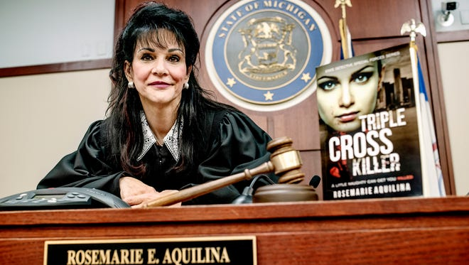 """Ingham County Circuit Judge Rosemarie Aquilina sits next to a copy of her book """"Triple Cross Killer"""" while posing for a portrait in courtroom on Thursday, Jan. 10, 2018, at the Ingham County Courthouse in Lansing."""