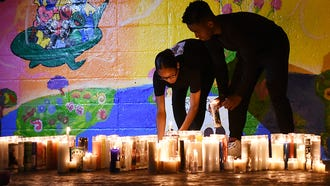 Vigil for Trinidad family at Votee Park in Teaneck on Saturday July 07, 2018. Audie Trinidad and his four daughters: Kaitlyn, 20; Danna, 17; and Melissa and Allison, 13-year-old twins, were killed in a automobile crash on Friday in Delaware. India Dearing and Donovan Florence place lit candles down at the vigil.