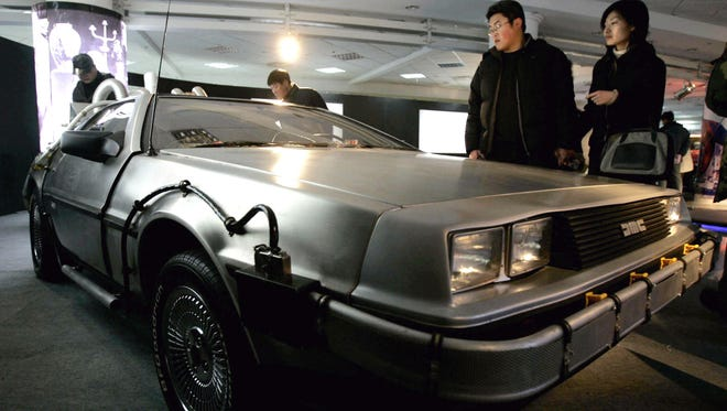 """Visitors look at a DeLorean used in the U.S. movie """"Back to the Future,"""" at International Classic Cars China Tour 2005 in Shanghai on March 5, 2005."""