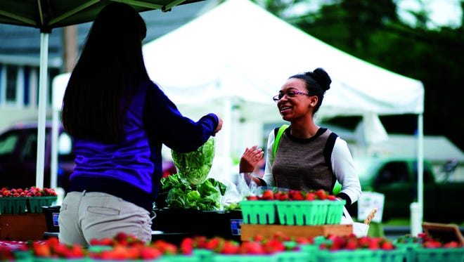 Michelle Rideau of Georgetown buys butterhead lettuce and broccoli from Evans Farms at the Milton farmers market.