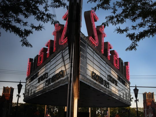 The marquee of the Strand Theater is reflected on its own exterior along Main Street in Brockport.