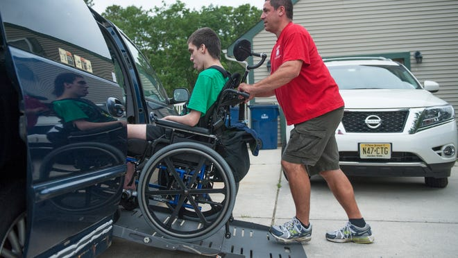 Dave Goldstein assists his 18-year-old son Joshua, who has Joubert syndrome, to enter their handicapped accessible van outside of their Voorhees home.  Joshua is confined to a wheelchair and his parents are raising money to buy a new handicapped accessible van because their current van requires costly upkeep which poses a financial strain on their budget.   05.27.14