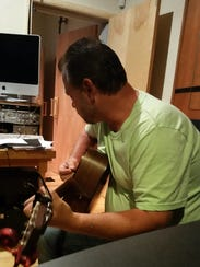 Raymond Govero plays guitar for an album he's hoping