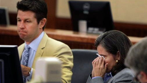 Dr. Ana Maria Gonzalez-Angulo, right, wipes her eyes after her defense attorney Derek Hollingsworth, left, finished his closing argument in her trial, Wednesday, in Houston. Gonzalez-Angulo, a breast cancer doctor, is accused of spiking researcher George Blumenschein's coffee in 2013 with a chemical found in antifreeze. Blumenschein survived.