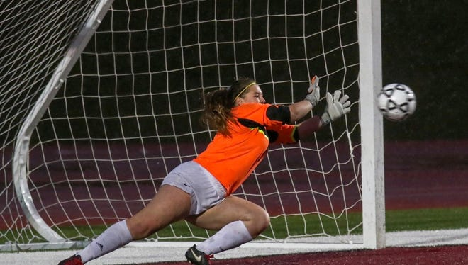 Ventura High goalkeeper Kambria Haughton dives to make the first of three straight shootout saves in the CIF Southern California Division IV regional final Saturday at Paloma Valley High in Menifee.