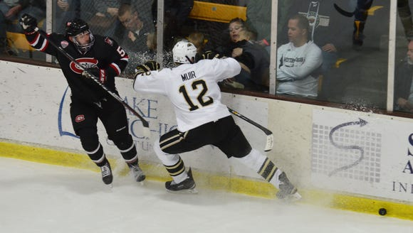 St. Cloud State's Nate Widman (5) pushes the puck past