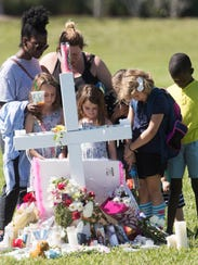 Mourners gather Friday, Feb. 16, 2018, at one of the