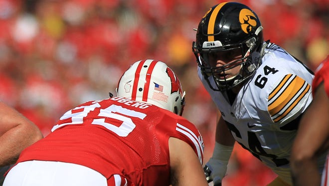 Iowa left tackle Cole Croston (64) lines up as C.J. Beathard calls for the ball during the Hawkeyes' game at Camp Randall in Madison on Saturday, Oct. 3, 2015.