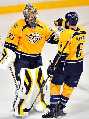 Predators goalie Pekka Rinne and defenseman Shea Weber celebrate a 3-2 win over the Minnesota Wild at Bridgestone Arena on Oct. 8, 2013.