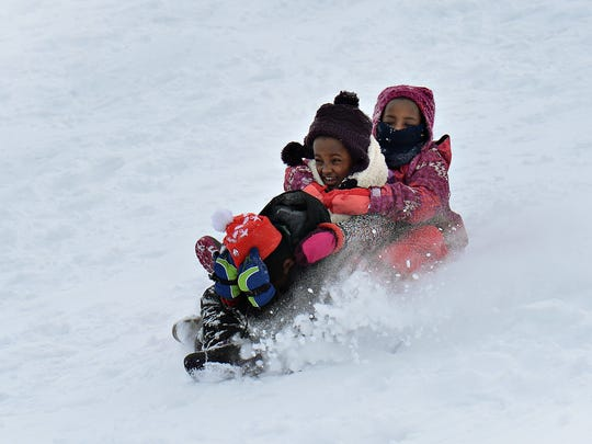 Nesha, left, and Sito McKay, both 8, sled with a friend