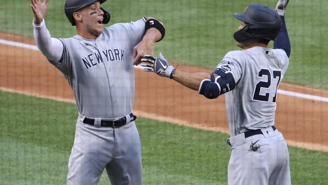 New York Yankees designated hitter Giancarlo Stanton (27) celebrates with right fielder Aaron Judge after hitting a two-run home run in the first inning Thursday against the Washington Nationals at Nationals Park in Washington.