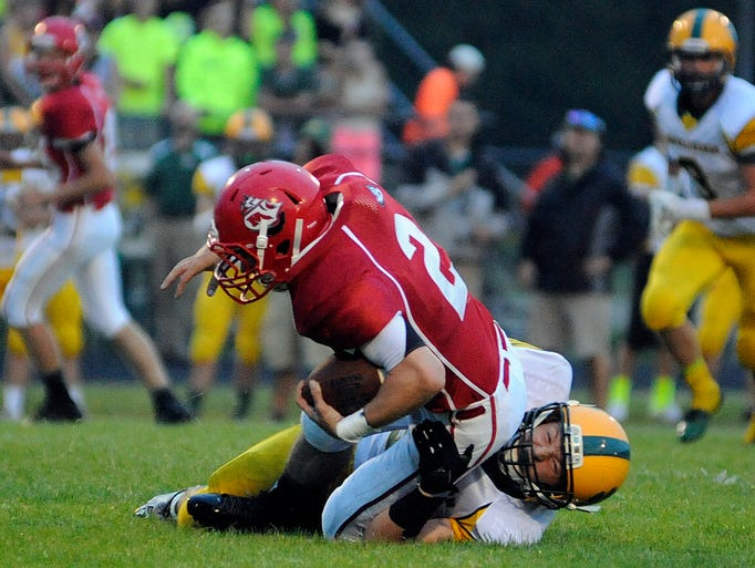Manitowoc Lincoln's Cameron Jaeger is tackled by Ashwaubenon's Ethan Grendziak during their football game on Friday, Aug. 29, 2014 at Ron Rubick Municipal Field in Manitowoc. Matthew Apgar/HTR Media