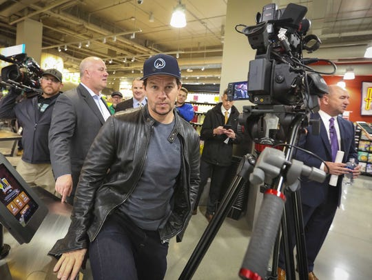 Actor/producer Mark Wahlberg sneaks in behind a news