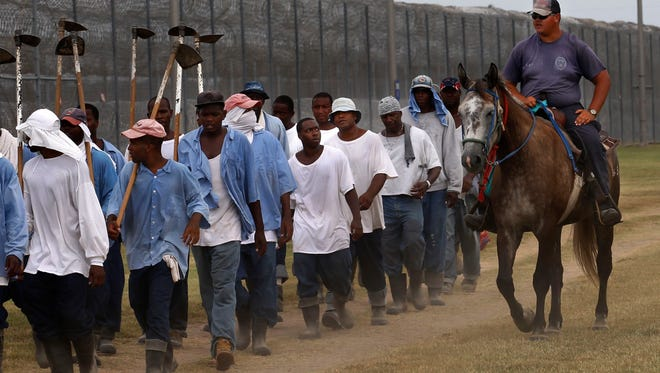 FILE - In this Aug. 18, 2011 file photo, a prison guard on horseback watches inmates return from a farm work detail at the Louisiana State Penitentiary in Angola, La. As summer approaches, corrections officials throughout the country must deal with prisoners? potentially fatal exposure to extreme heat. Advocates say rising temperatures are a threat to an increasingly mentally ill and aging prisoner population. Lawsuits over heat conditions in jails and prisons have been filed in Arizona, Wisconsin, Illinois, Louisiana, Georgia and Delaware. (AP Photo/Gerald Herbert, File)