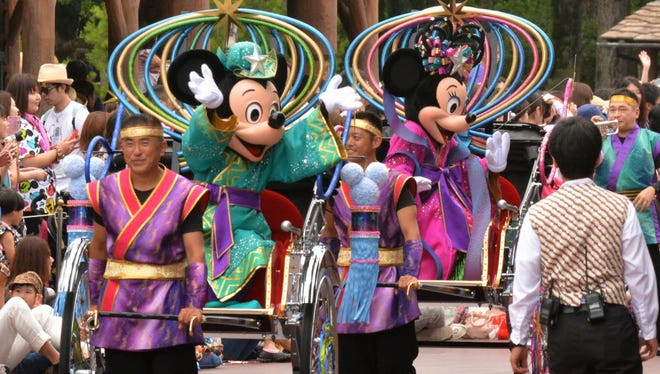 """Disney characters Mickey Mouse (2nd L) and Minnie Mouse (2nd R) dressed in """"Tanabata"""" or the Star Festival costumes wave from rickshaws as they greet guests along the parade route at Tokyo Disneyland in Urayasu, suburban Tokyo on June 30, 2015. Tokyo Disney Resort announced that the program """"Disney Tanabata Days"""" will be held at both Tokyo Disneyland and Tokyo DisneySea Parks until July 7.    AFP PHOTO / KAZUHIRO NOGIKAZUHIRO NOGI/AFP/Getty Images ORIG FILE ID: 542163953"""