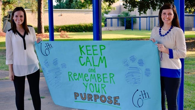 """Alexandria Middle Magnet School sixth-grade professors Paige Bruce (left) and Jessica Stewart welcome students Monday morning with a sign reminding kids to """"keep calm and remember your purpose."""""""