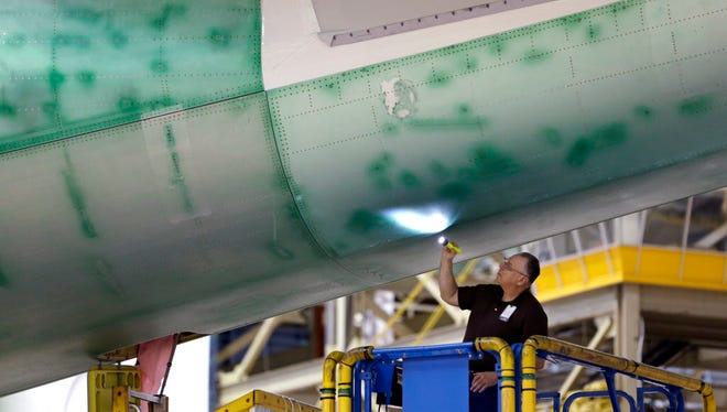 In this photo taken Wednesday, May 29, 2013, a Boeing employee uses a flashlight to inspect the underside a Boeing 747 jet being assembled at the company's production plant in Everett, Wash.