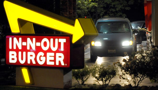 In this June 8, 2010, file photo, a customer receives an order from the drive-through at an In-N-Out Burger.
