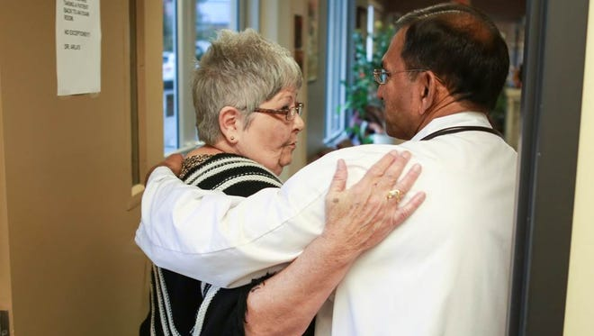 Pam Woods is comforted by Bullitt County Kentucky family practitioner Mohana R. Arla as she leaves his office on Oct. 31, 2014. Pam and husband Bernard Woods are battling Bernard's stage three colon cancer and carcinoid cancer of the lungs.