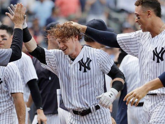 In this July 8, 2017, file photo, New York Yankees' Clint Frazier, center, is congratulated by teammates, including Aaron Judge, right, after hitting a three-run walkoff home run during the ninth inning of an interleague baseball game against the Milwaukee Brewers, at Yankee Stadium in New York. Frazier is batting .292 (7 for 24) with six extra-base hits, including three homers, since being called up July 1 following a rash of injuries in the Bronx.