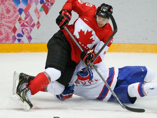 FILE - In this Feb. 13, 2014 file photo, Canada forward John Tavares loses his footing against Norway defenseman Ole-Kristian Tollefsen in the third period of a men's ice hockey game at the 2014 Winter Olympics in Sochi, Russia.  Tavares says he and other players in the league want the NHL to let them participate in a sixth straight Olympics. The union representative, though, knows the stay-or-go topic has become a bargaining chip for the league and NHL Players' Association.(AP Photo/Mark Humphrey)