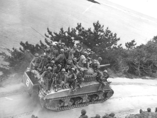 Sitting on a tank, these U.S. infantrymen are seen on their way to take the town of Ghuta on Okinawa, on April 1, 1945. (AP Photo)