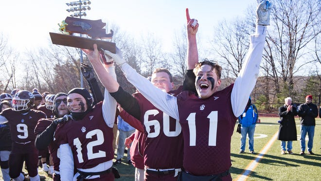 Leicester High football captains Daniel Mero, Jack Larson and Jack O'Neill celebrate the Wolverines winning the Division 7 Central championship last season.